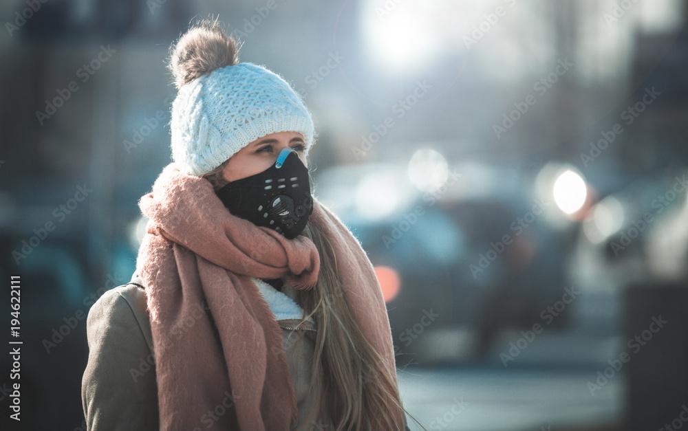 Młoda kobieta jest ubranym maskę ochronną w ulicie miasta, smogu i zanieczyszczeniu powietrza