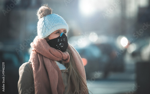 Obraz na plátně Young woman wearing protective mask in the city street, smog and air pollution
