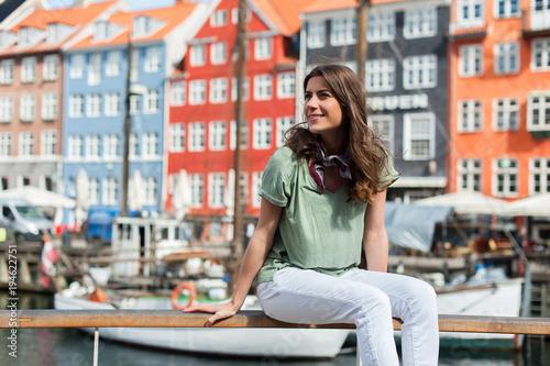 Young tourist woman, sitting at the Nyhavn harbor pier Copenhagen, Denmark Poster