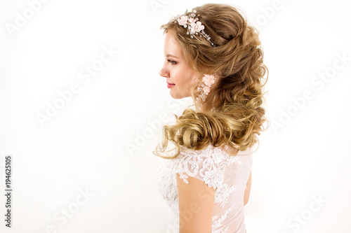 Photo  young blonde girl in a white wedding dress and jewelry in hairstyle  with big cu