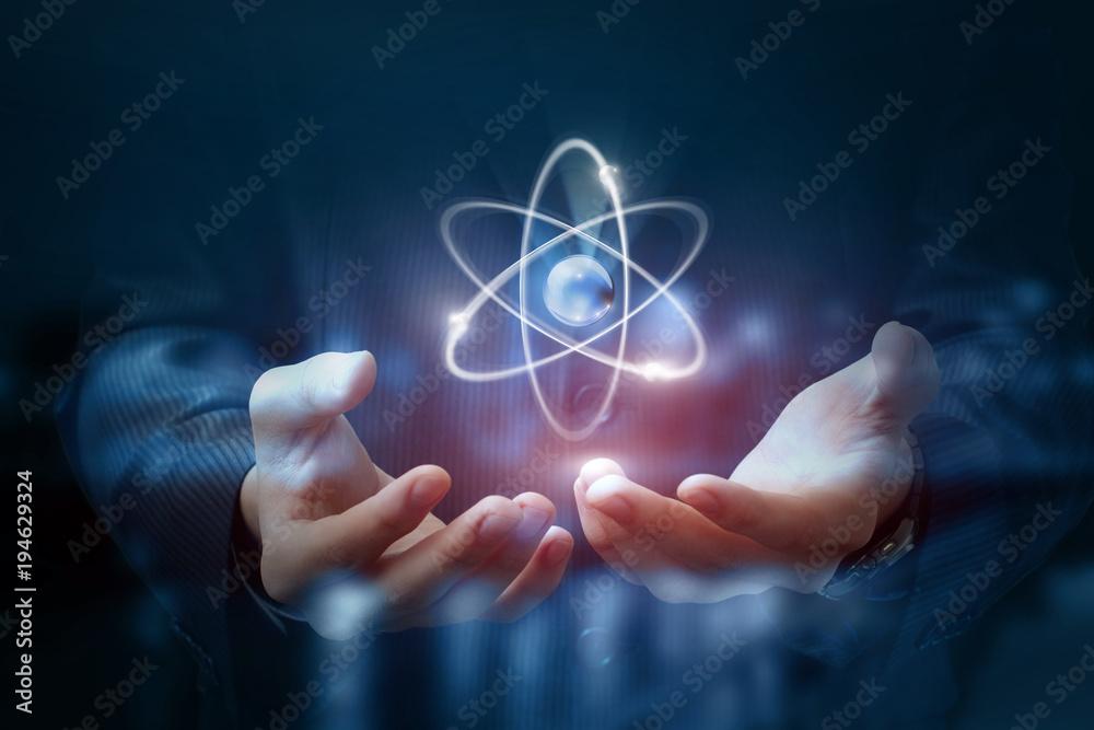 Fototapeta Hands shows the atom .