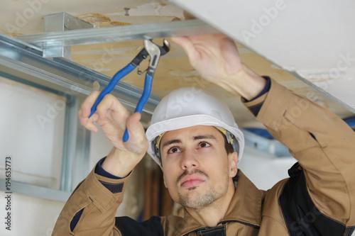 Workman using pliers on metal framework Tableau sur Toile
