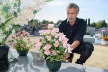 Man Arranging Flowers On Tomb