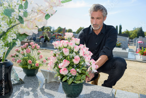 Fotografie, Obraz  Man arranging flowers on tomb