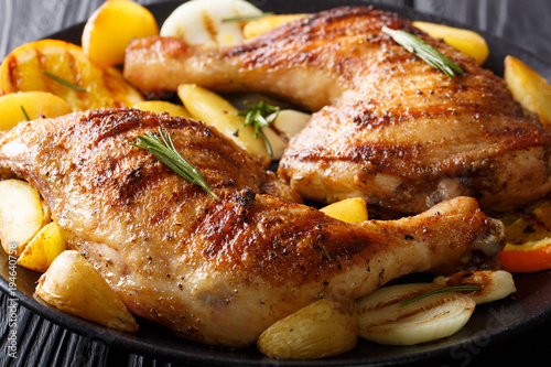 Fotografía  grilled chicken leg with oranges, onions and potatoes macro