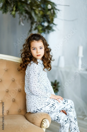 A Photo Of A Beautiful Little Girl With Blue Eyes And Brunette Curly Hair In Studio Sitting On The Sofa And Smiling