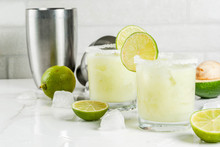 Alcoholic Cocktail Recipes And Ideas. Avocado And Lime Margarita With Salt, On A White Marble Kitchen Table. Copy Space