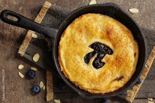 Fotografija  Pi Day special homemade blueberry pie baked in a skillet overhead view