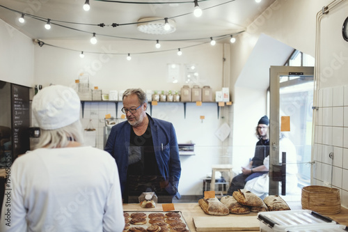 Male customer buying food from owner at bakery