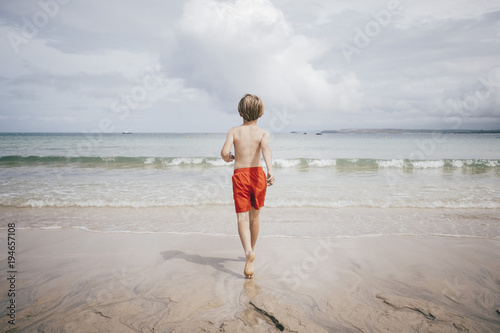 Rear view of shirtless boy walking on shore at beach against sky