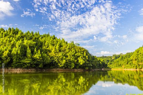 Fototapeta Calm lake and green hills in summer sunlight obraz na płótnie