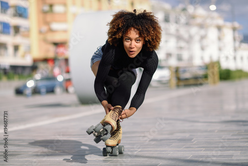 Fotografía Black woman on roller skates riding outdoors on urban street
