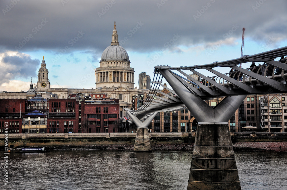 Millenium bridge view with St Paul's Cathedral in the back and Thames river. Cloudy and cold winter day.