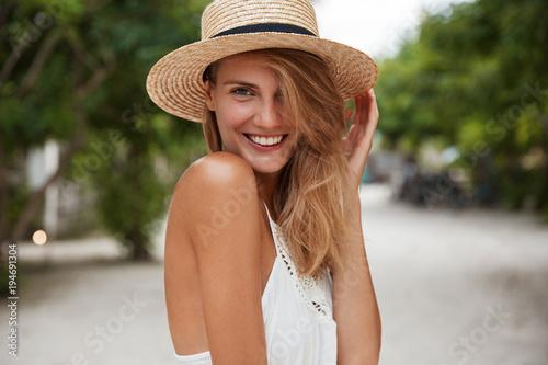 Foto  Außenaufnahme der schönen jungen glücklichen Frau mit breitem glänzendem Lächeln