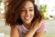 Shot of adorable beautiful smiling female with Afro hairstyle, dressed in striped t shirt, has positive and dreamy expression, thinks about something plesant. Young woman with shining broad smile