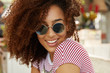Cheerful dark skinned female with curly hair, wears sunglasses and striped t shirt, being in high spirit as meets with friends in cafeteria, enjoys resort and summer vacations. Rest, emotions concept