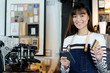 Young asian woman barista using smartphone and holding credit card at cafe counter, food and drink business concept
