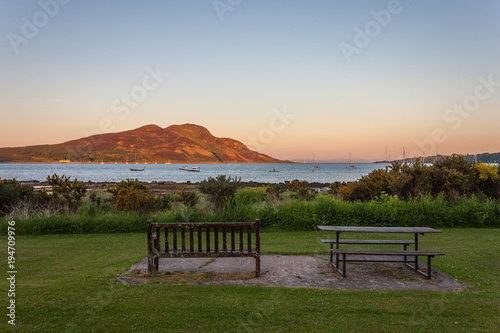 Photo Bench and Picnic Table looking out to Sea and Island at Sunset