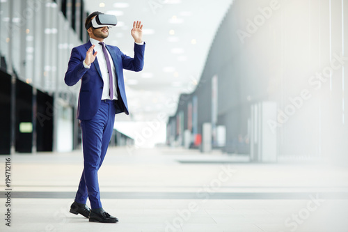 Cuadros en Lienzo Businessman in elegant blue suit and vr headset taking part in virtual conferenc