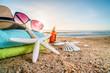 Sunglasses, towels, hat, sun block, shells and starfish on sandy beach