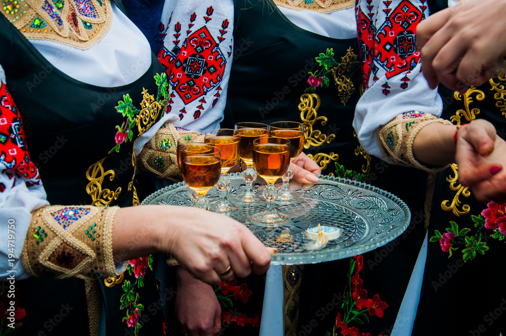 Fototapeta Women in traditional ethnic Ukrainian  costumes with patterns holding a silver tray with glasses of wine or cognac