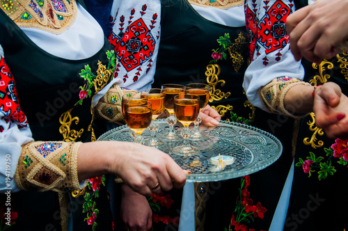 Obraz Women in traditional ethnic Ukrainian  costumes with patterns holding a silver tray with glasses of wine or cognac - fototapety do salonu