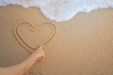 Hand Of The Women Drawing Heart Shape  On The Sand Of A Beach With Wave Of The Sea.