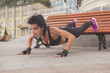 Brunette slim adult sexy fit sporty caucasian woman in sportswear on a european city streets in morning do exercises (workout) - push ups. Copy space