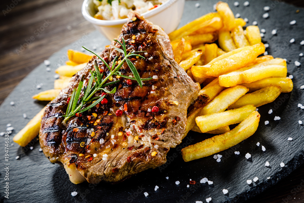 Fototapety, obrazy: Grilled steak with french fries and vegetables served on black stone on wooden table