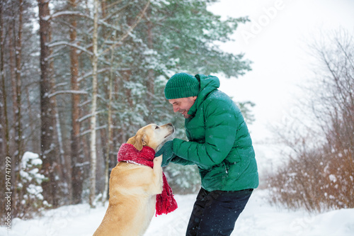 Fotografía  Happy smiling man with Labrador retriever dog playing in snowy pine forest in winter