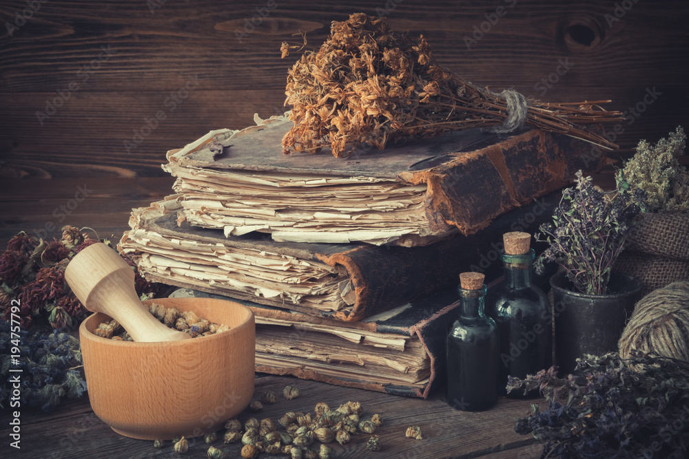 Fototapety, obrazy: Tincture bottles, bunches of dry healthy herbs, stack of antique books, mortars, sack of medicinal herbs. Herbal medicine.