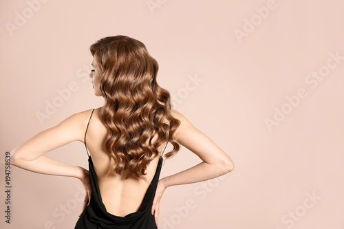 Foto auf Leinwand Friseur Beautiful young woman with long wavy hair on light background