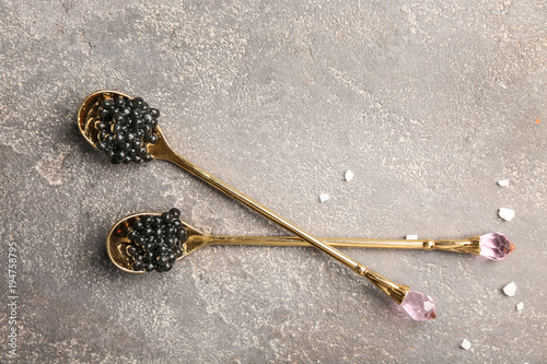 Spoons with delicious black caviar on grey background