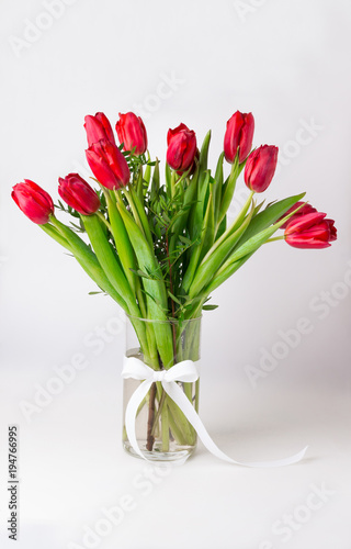 Poster Fleuriste Bouquet of red tulips in vase white satin ribbon isolated.