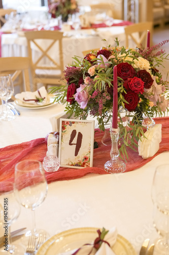Set of wine flowers on a wedding table surrounded by plates, tablecloths and candles. Interior. Copy space
