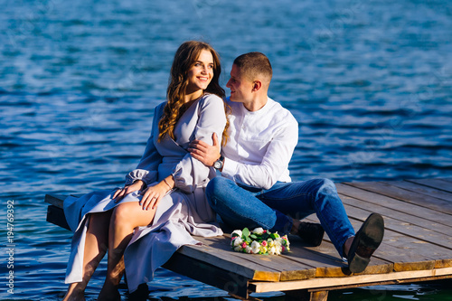 Garden Poster Water Motor sports beautiful girl with long hair sitting on the pier of the lake an
