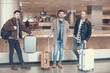 Full length portrait of outgoing male friends standing in airport. Vacation concept