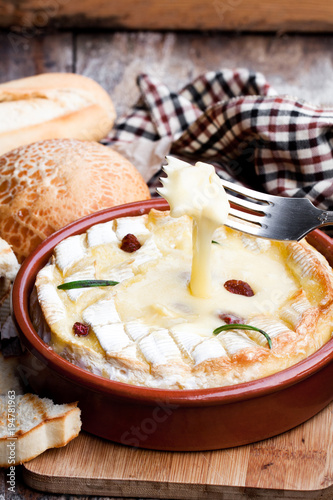 Delicious  hot baked camembert with sultanas on wooden table