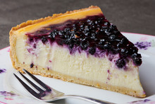 Piece Of Blueberry Cheesecake On A Plate With A Silver Fork