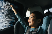 Little Asian Boy Smiling Out Car Window Inside Car Wash