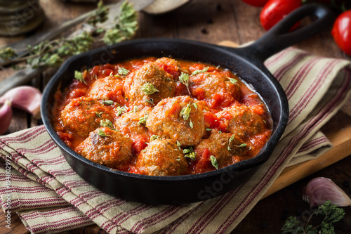 Meatballs in tomato sauce with dried oregano in a rustic vintage cast iron skill Obraz na płótnie