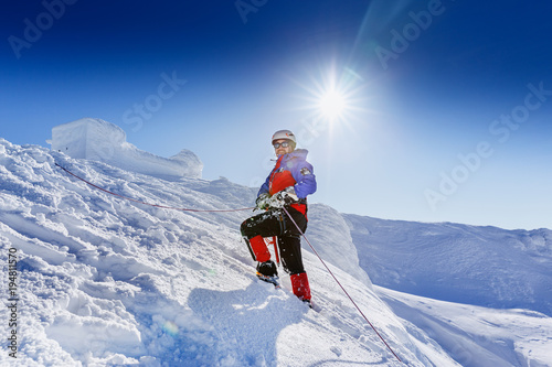 In de dag Alpinisme Equipped climber ascent by snowy slope with climbing rope on the top of peak in snowy alpine mountains. Life guard professional man on the work in high mountains. Action in hard conditions scene.