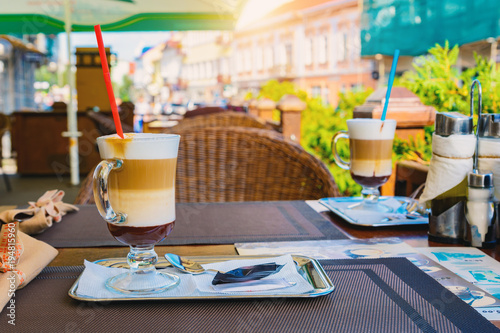 Poster Cracovie A cup of cappuccino on the table of a street cafe