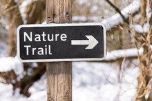 Nature Trail Sign On A Hiking Path In A Snow Covered Forest