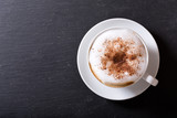 Cup of cappuccino coffee on dark table