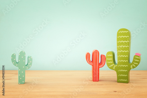 Image of colorful cactus decoration infront of wooden blue background.