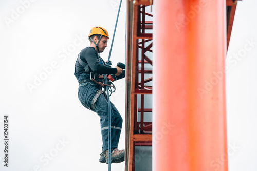 Industrial climber hangs a poster on a billboard Canvas Print