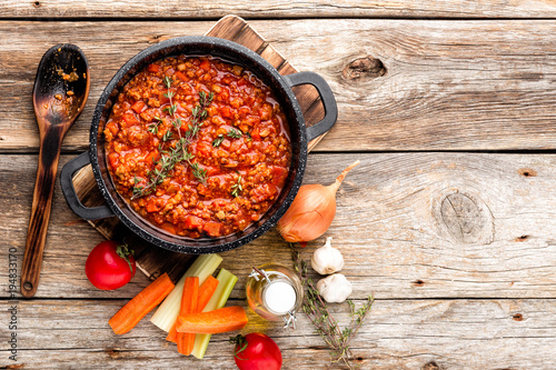 classic italian bolognese sauce stewed in cauldron with ingredients on wooden table, top view, culinary background with space for text