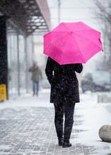 Woman With Pink Umbrella On Snowy Day.