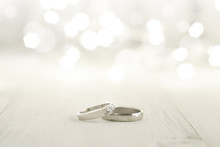 Two Wedding Rings Place On Wooden Floor With Light Bokeh Background.